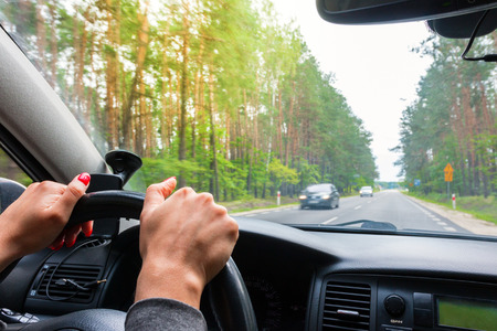 overtaking: Woman holding steering wheel, drives the car