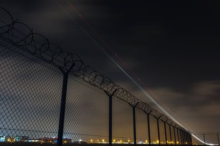 Fence with barbed wire, restricted area and starting plane *** Local Caption *** Fence with barbed wire, restricted area and starting plane Stock Photo