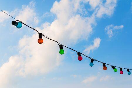 Colorfull lightbulbs against blue sky