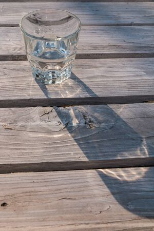 Glass of water casting shadow on wooden table