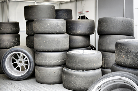 tire fitting: Stack of threadbare wheels on backstage of car races Stock Photo