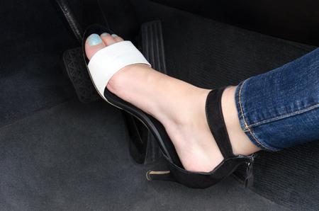 Women's leg pushing the break pedal in the car