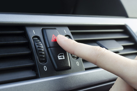 flashers: Finger pushes car emergency lights button
