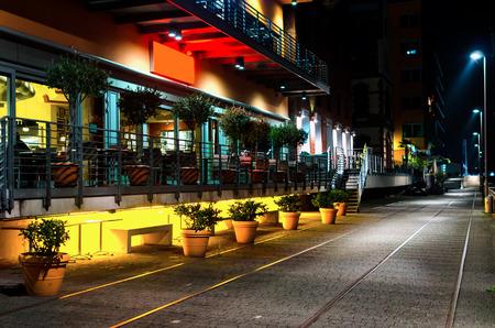 夜照明にトラム方法と道路の近くの街で屋外カフェヴィンテージ効果