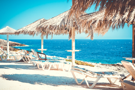 Exotic beach with sunbeds under umbrellas. Paradise place near the sea. Summertime vacation holidays concept Stock Photo