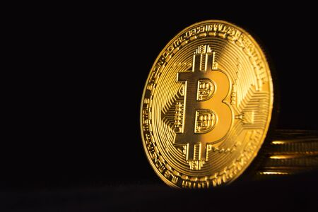 Bitcoin in the dark. Close up view on heap of golden bitcoins. Black background with copyspace