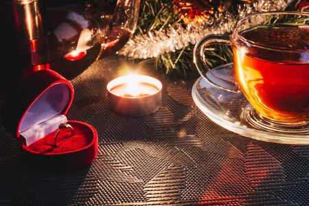 Engagement ring in velvet red box on the table near Christmas decorations, cup of warm tea and candle. Wedding proposal on Christmas eve.