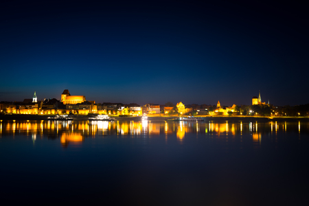 Night panorama of Torun city. Gothic architecture in Old Town illuminated at night