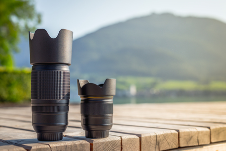 Zoom lens and lens with fixed focal length from digital camera standing on wooden board with mountain landscape at background