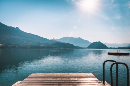 Beautiful sunrise above the alpine valley. Wooden pier on mountain lake in Alps