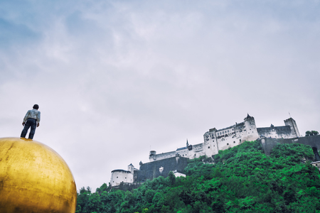 Figure of man standing on golden ball looking on at rainy day. Salzburg, Austria