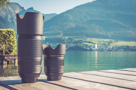 Digital camera lenses standing on wooden board with mountain landscape at background. Copy space background. Vintage filter 写真素材