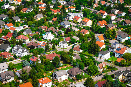 Suburban neighborhood with modern living residential houses. Ecologically clean places for living. Solar batteries on the roofs. Suburban infrastructure. Aerial view.