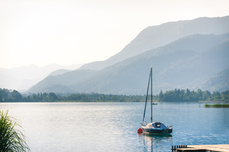 Beautiful landscape with yacht on the lake in mountains at summer morning
