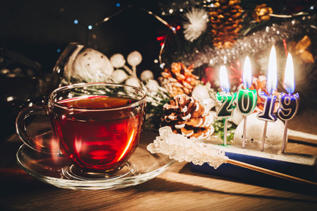 New year 2019 candles burning near the cup of hot tea and Christmas tree 写真素材