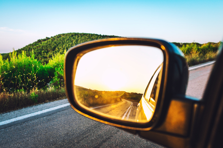 Bright sunset reflected at side view mirror of moving car by mountain road 写真素材
