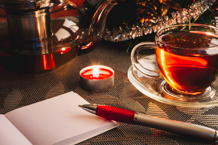 Cosy Christmas. Wishlist on the table near Christmas tree and cup of hot tea. Copy space 写真素材