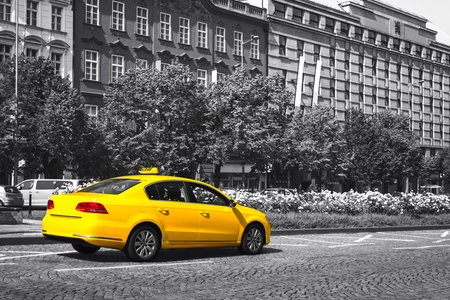 Yellow taxi parked on city street. Black and white. Selective color effect