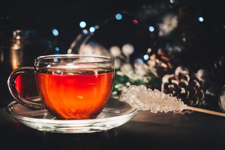 White sugar crystal near glass cup of hot tea; Winter still life; Postcard