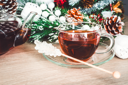 Hot cup of black tea and white sugar on a stick. Christmas decorated still life
