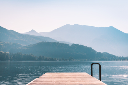 Wooden pier on the lake with mountain scenery in Alps at sunrise 写真素材