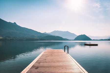 Long wooden pier on Wolfgangsee lake in Austrian Alps. Calm morning scenery 写真素材
