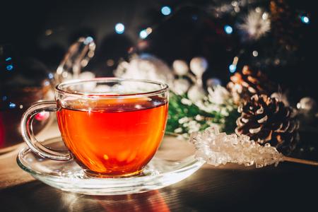 Bright shining cup of hot tea in dark room. Spending winter evening at home 写真素材