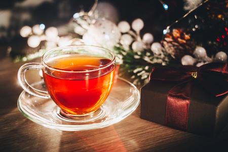 Cup of hot tea and small box with present near Christmas tree. Christmas postcard 写真素材
