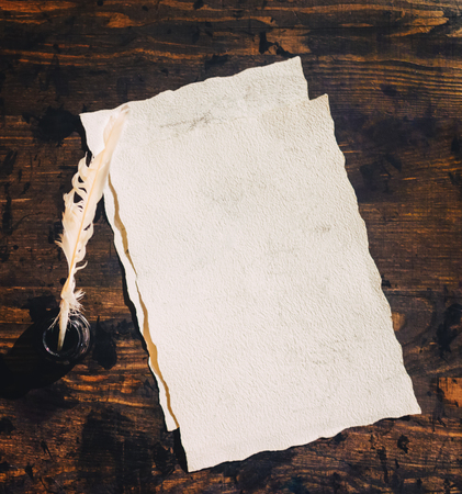 Blank sheet of parchment paper with ink and quill pen on wooden table. Top view. Copy space for text. Background for demonstration of font or logo. Vintage photo