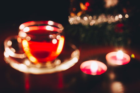 Defocused abstract blurred Christmas background with hot cup of tea and lights in bokeh