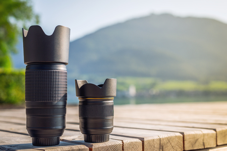 Lenses of photo camera standing in a row. Zoom tele lens and wide angle lens with fixed focal length from dslr camera 写真素材