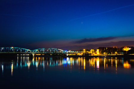 Panorama of night city from the bank of the river with illumination and star sky