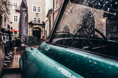 Side of vintage car in rain drops parked on narrow city street; Abstract vintage background 写真素材