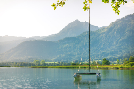 Yacht standing at the mountain lake with transparent water in Alps at sunrise