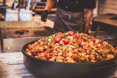 City street cooking in europe. Street food. Cook preparing big plate of meat. 写真素材