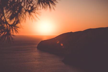 Orange sunset on the sea background. Summer vacation traveling. Vintage photo