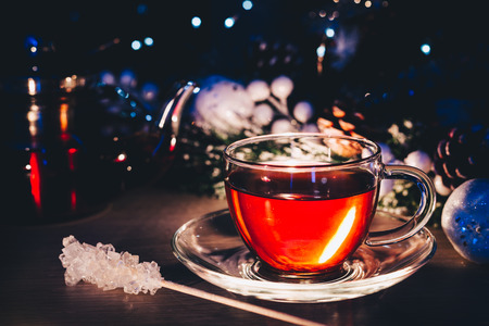 Glass cup of hot tea with white sugar on stick at dark room decorated with Christmas lights