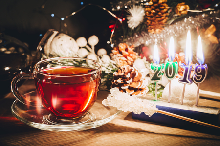 2019 year is coming. Nice candles burning near Christmas tree and cup of tea. Happy New Year