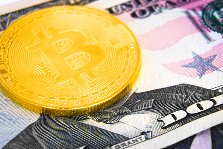 Golden bitcoin coin on US dollar banknote 写真素材