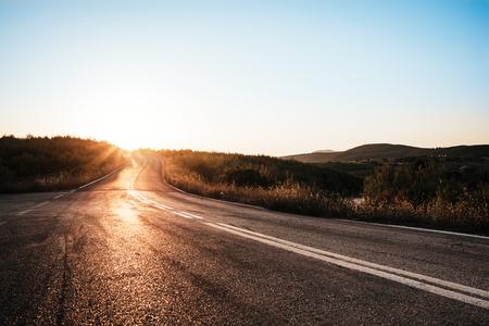 Winding asphalt road at rays of sunset; Summer traveling background landscape 写真素材