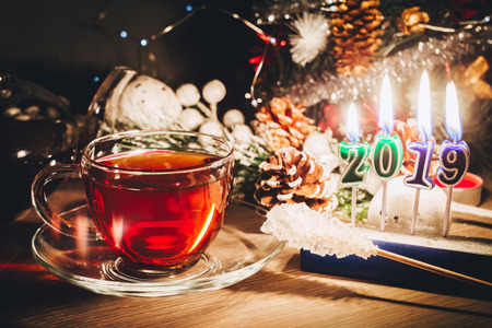 New year card with cup of tea near decorated christmas tree and burning candles 2019. Happy New Year