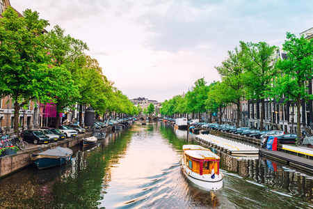 Channel in Amsterdam at sunset. Boat going down the river in Amsterdam. Picturesque cityscape of Amsterdam streets.