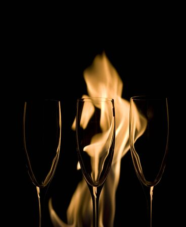 Three Crystal glasses and fire isolated on black   photo