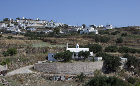 Small Orthodox Church in front to typical Cycladic town Stock Photo