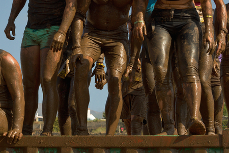obstacle: Group of people jumping over an obstacle mud run During the Inferno race