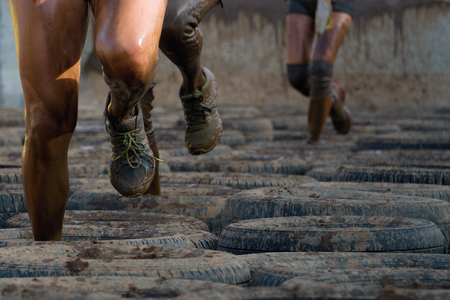 runners: Mud runners race, tries to make it through the pull trap Stock Photo