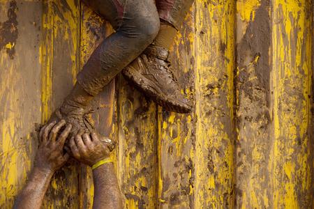 coureur: Mud coureurs assistance en course pour la percée Banque d'images