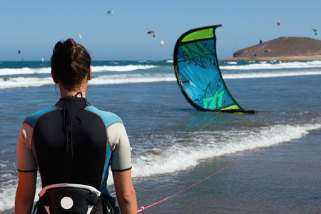 A young woman ready for kite-surfer kite surfing rides in blue sea Stock Photo