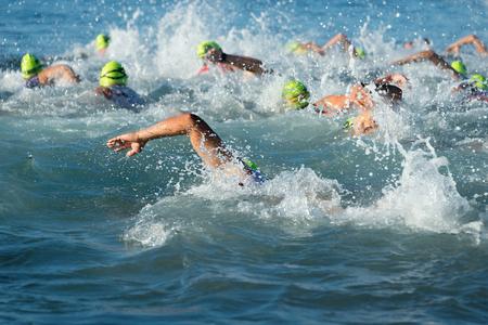 Groep mensen in wetsuit zwemmen bij triathlon Stockfoto