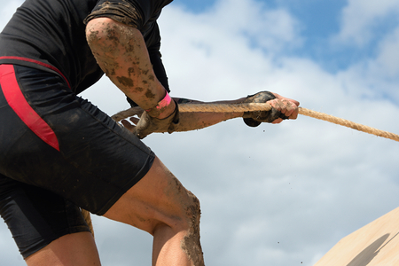 Mud race runners.Racing- overcome barriers using ropes Archivio Fotografico